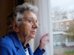 Elderly person looking out of a window