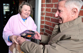 Elderly woman receiving a meal sent to her house