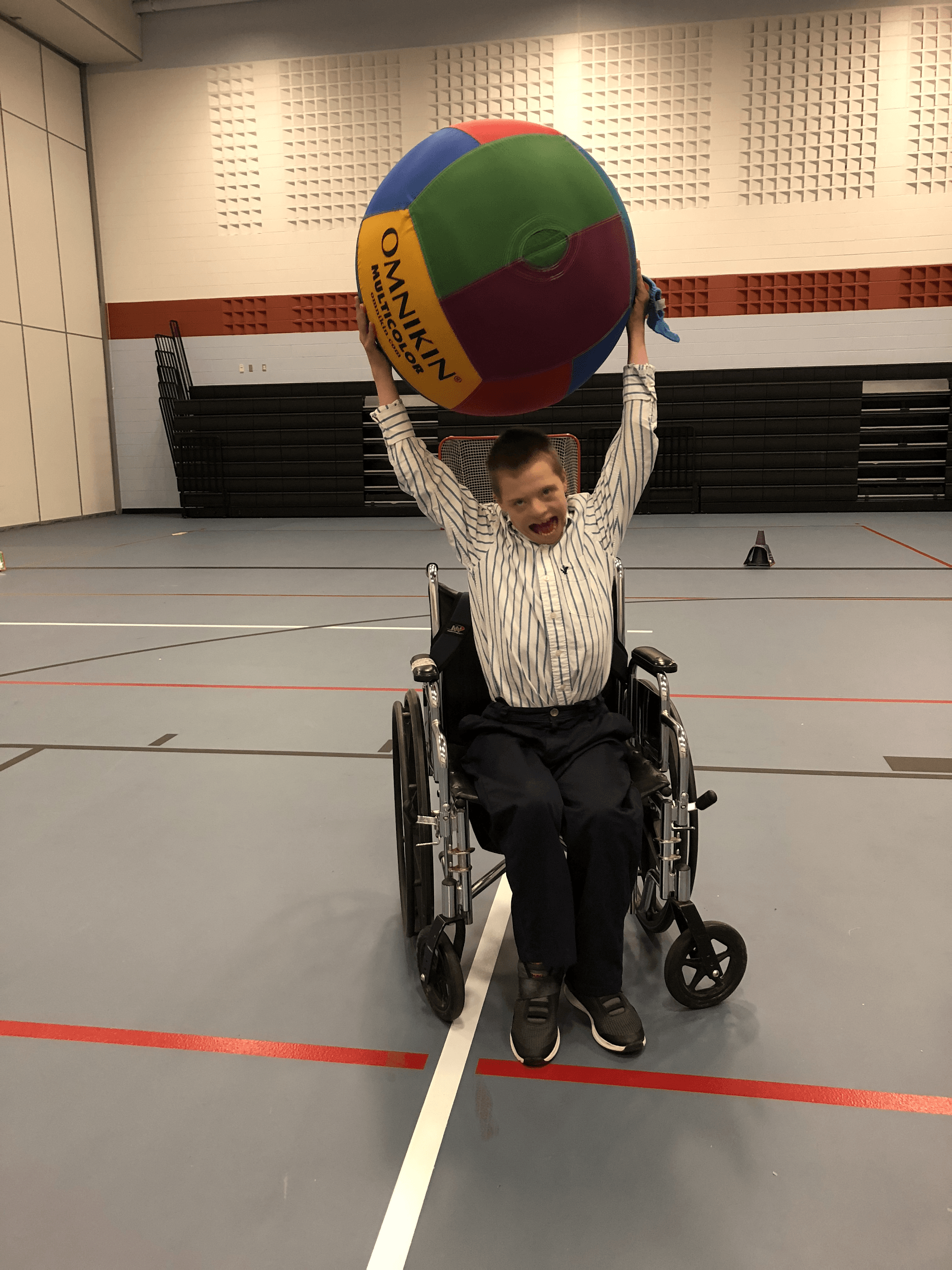 Student in wheelchair holding up exercise ball